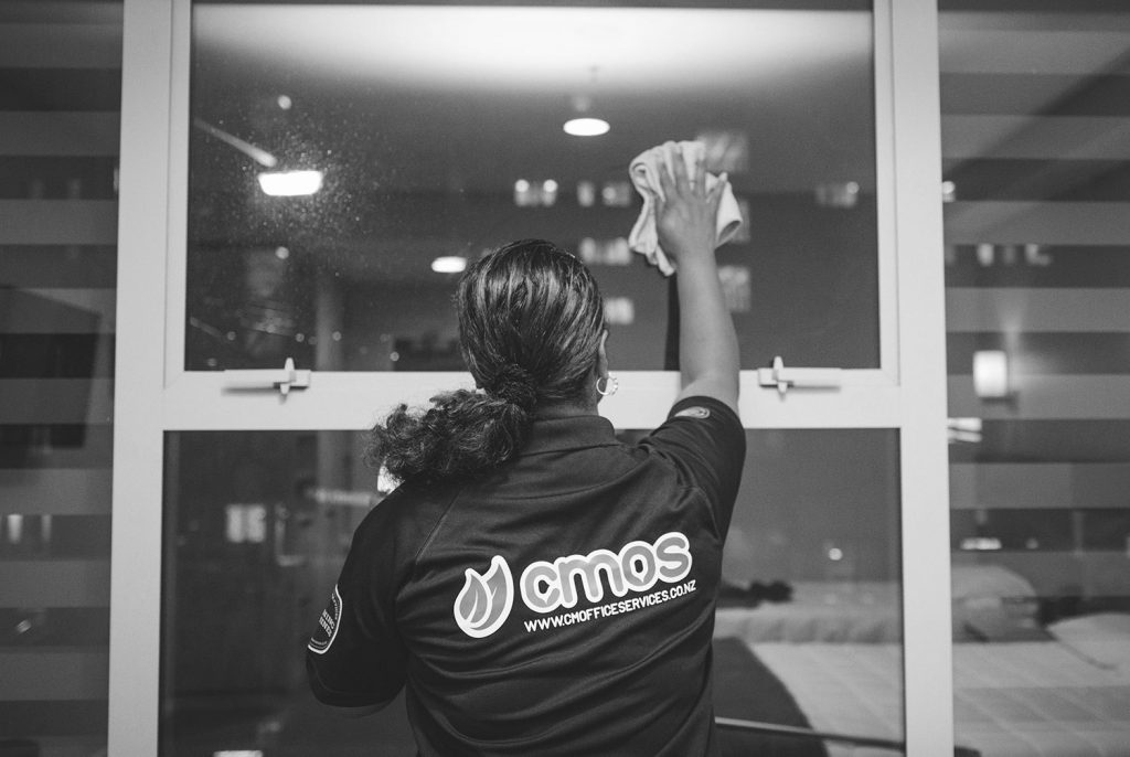 A CMOS team member cleaning a window